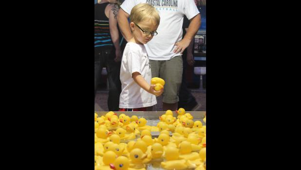 Deegan Stoffel retrieves a duck to turn in for a prize on the midway at the Rock County Fair Thursday night.