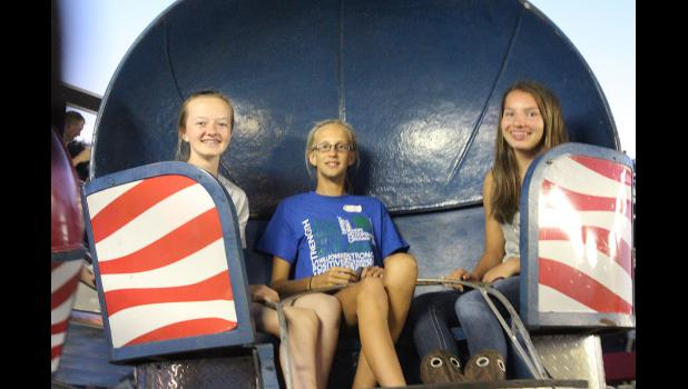 Riley Severtson, Whitney Elbers and Mackenzie Peterson wait for their ride to start on the Tilt-A-Whirl at the Rock County Fair Thursday night.
