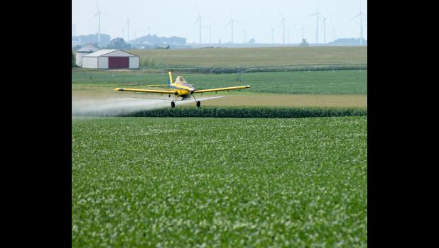 Pilot Matt Schanilec from AgriMAX LLC, Grafton, North Dakota, sprays a soybean field north of Kenneth earlier this month. According to aerial application manager JP Knox, his company sprayed about 25,000 soybean acres for aphids in a two-week timeframe. The amount is comparable to previous years in Rock County.