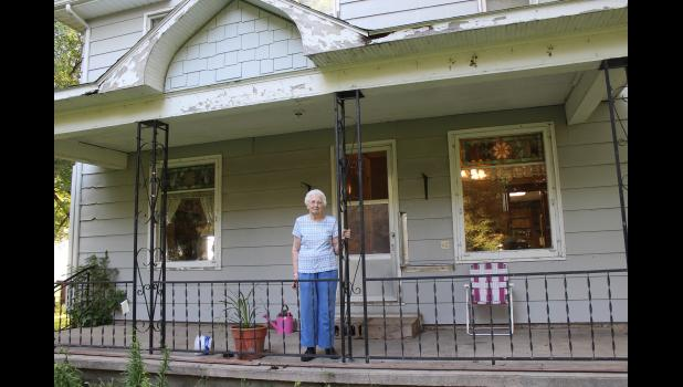 Jessie Wenzel poses on the front porch of her rural Denver Township home near Hardwick, the only home she has lived in since her birth 86 years ago. Last week Wenzel moved to Luverne.