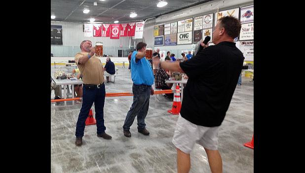 Jason Schultz (left) and Mike Davis (center) duke it out in the first Stein-Holding Contest as organizer Rick Peterson encourages the men's division finalists to keep their glass steins at shoulder level. The contest was part of Rock River Beerfest activities Saturday afternoon at the Blue Mound Ice Arena in Luverne.