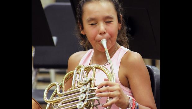 Roselynn Hartshorn concentrates on reaching the correct pitch during her third band lesson on the French horn.