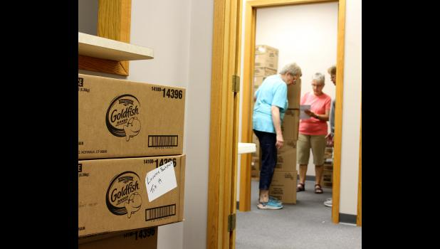 Volunteers with Luverne's Backpack Program Carol McDonald (left), Shirley Klosterbuer, Lona Klosterbuer and Rhonna Jarchow (not pictured) sort through food boxes last week at the program's downtown storage room for food items that are distributed at the middle/high school.