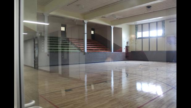 Pictured through locked glass doors, the original gymnasium looks much like it did when the building was an elementary school.
