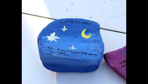 "Students painted rocks with various designs and messages such as ""Spread the Joy"" and "" Shoot for the moon … even it you miss, you land among the stars."""