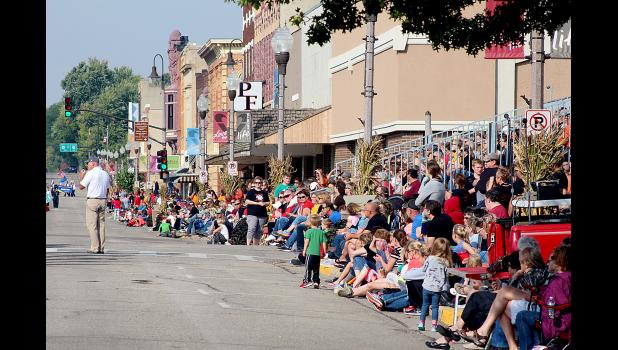 Crowds soak in the early autumn sunshine on the parade route.