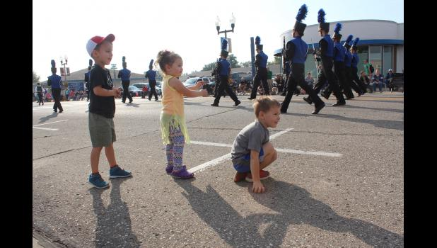 Colton Corn, Mila Hawkins and Sullivan Benjegerdes anticipate the nest band approaching them on Main Street Saturday.
