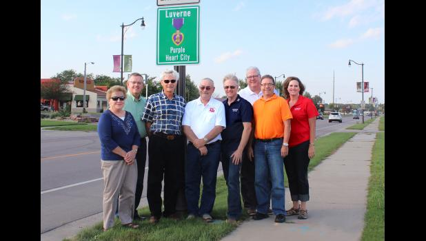 Luverne City Council members and local veterans dedicated Luverne as a Purple Heart City Tuesday night at the signage on South Highway 75. From left are City Councilwoman Esther Frakes, Mayor Pat Baustian, veterans Gary Hassebroek and Buck Underwood, Councilman Kevin Aaker, City Administrator John Call and council members Eugene Marshall and Caroline Thorson.