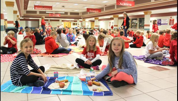 Luverne Elementary second-graders (from left) Molly Boltjes, Annie Smeins and Cali Syndergaard have a picnic lunch together with their classmates and the third-grade class in the first of three lunch hours Friday in the school commons.