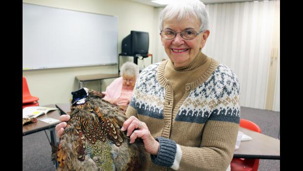 Donna Landsman of Luverne holds one of the feather pelts she dried and has stored for at least 20 years.
