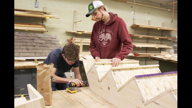 Building construction students Brandon Mills (left) and Riley Siebenahler work Tuesday morning on the steps needed for the high school musical set. This is the first year students in Darrel VanAartsen's woodworking classes constructed the sets needed for the school's theatrical performances.