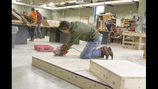 Luverne High School senior Tyler Roberts uses the skill saw Tuesday morning to even the sides of the platform that will be used in the upcoming high school musical performance on Nov. 7-9.