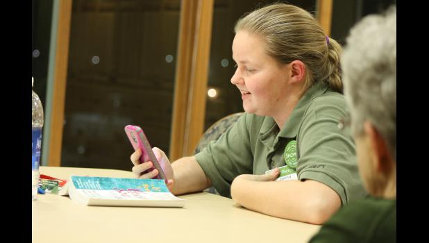 Using her smart phone, Jenna Schelhaas looks up information during a Sunday evening Senior Book Club discussion. The book club takes place at the Mary Jane Brown Home, and while anyone can attend, it is mainly attended by MJB residents.