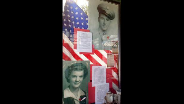 """In Ruth Brown's Alamosa, Colorado, store window is a tribute to her late family members including """"Dad's Story"""" and his picture that encourages others to fly a flag on Dec. 19 in honor of her dad and all veterans. Her mom, Betty, is also pictured."""