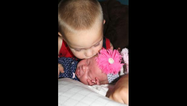 Two-year-old Coyer gives his sister Hazyl a kiss.