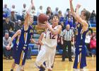 Hills-Beaver Creek guard Preston Wilhelmi works his way between Adrian defenders Christian Weidert and Ryan Wieneke during Tuesday game in Adrian.