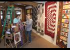 Joyce Fluit (left) and Verla Fick, members of the Blue Mound Quilters, set up the club's challenge display that had members incorporating the same polka dot-patterned fabric in a quilt project no larger than 24 inches.