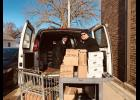 Wyatt Sprecher (right) and Billy DeBates unload a van full of food donations in the alley behind the United Methodist Church, which houses the food shelf.