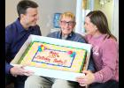 Helmer Haakenson receives assistance holding a cake in honor of his 100th birthday on Feb. 20 by his two youngest children Mike (right) and Mary.