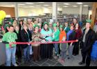 Luverne Area Chamber President Kullen Schroht (far left) and past president Mike Smith (far right) hold the ribbon for the Rock County Community Library's ribbon-cutting ceremony on St. Patrick's Day March 17. Pictured from left is Faye Bremer, Schroht, Annie Opitz, Heidi Sehr, Joyce Oldre, Lauri Ketterling, Tina Petronek, Patti Olson, Gloria Rust, Commissioner Ken Hoime, Bruce Olson, Bronwyn Wenzel, Camilla Graff, Linda Gulden, Ryan Wynia, Serena Gutnik, Dolly Remme, Barb Verhey, Meredith Vaselaar, (little