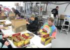RCO clients (from back to front) Kristi Brandt, Casey Van Engelenhoven and Doug Dysthe assemble boxes at Take 16 brewery in Luverne Friday morning.