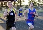 Hills-Beaver Creek's Trenton Bass keeps pace with an Edgerton-Southwest Christian athlete during the 400-meter dash at the Cardinal Relays in Luverne April 12.