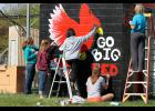 As part of Senior Service Day, the equipment shed receives a new coat of paint and cardinal design. This year's design was by Spencer Schacht, and helping paint on Friday, May 1, were (from left) Tennessee Bruhn, Alexis Hanson, Jessica Limones, Brooke Nattress and Alexis Hiller.