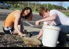 Seniors Sandra Renken (left) and Brandon Oakley pull weeds in Sanford Luverne's Healing Garden.