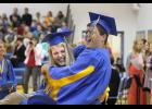 Tony Sieve celebrates with a jump into the arms of classmate Katie Wieneke during the recessional at Adrian High School.