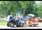The Bos Dairy Farm parade entry featured Caleb Bos driving the ATV with Amber Bos and Annie Bos riding with him pulling a baby dairy calf in a trailer.