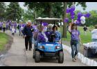 Honorary Chairwoman Merecie Domagala (far right) leads the survivors lap during Saturday night's Relay for Life event at the Luverne City Park. In the golf cart is Domagala's father-in-law, Del, also a cancer survivor, with his daughter Faye Bremer driving.