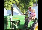 Luverne's Cory Johnson and his daughter Kali, 3, ride on an early model John Deere tractor in the Hardwick parade.