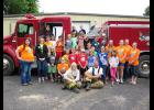 Safety Survivors Day Camp participants and Rock County 4-H ambassadors pose with Hardwick volunteer firefighters (sitting in front) Chelsey Javner and Lowell Schelhaas. Pictured behind the firefighters (first row, left) are Erica Lysne, Mary Christians, Jaycee Chapa, Thea Richards, Blake Sauer, Jaydon Johnson, Maddox Miller, Ava Steinhoff, Lydia Schuld, Rachel Graves; (second row, behind volunteers) Anja Jarchow, Larissa Steinhoff, Layke Miller, Mitchell Sauer; (third row) Kris Severtson, Coulter Thone, Ter