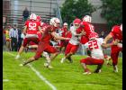 Luverne's Ashton Sandbulte fights his way through Redwood Valley defenders during Thursday night's home game on a wet Cardinal field. Luverne lost the game 20-6.