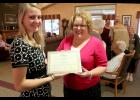 Nursing student Krista Stenger receives a scholarship plaque from Jill Schewe of Minnesota Care Providers Friday morning in the lobby of Poplar Creek apartments.