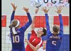 Luverne's Madison Crabtree spikes the ball between H-BC blockers Sidney Fick (10) and Mekayla Kolbrek during Tuesday's volleyball match in Hills.