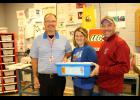 Lucas Peters (right) with the Rock County Soybean Growers Association presents graphic arts teacher Bill Thompson and school social worker Stacy Schepel with a start-up kit for the new after-school LEGO League beginning this month.