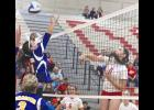 Luverne's Greta Ahrendt slips the ball past Adrian blocker Avery Balster during Tuesday's volleyball match in Luverne.