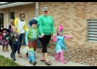 Lennox Ganun (far right, dressed as Princess Poppy) waves to a resident watching the Halloween parade walk through a window. Lennox walks with her mom, Kiley, and brother, Case, dressed as Branch the Troll. Behind the Ganuns are Otto (left) and Lexi Smook.