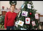 Lorraine Stoel poses with her winning entry in the Carnegie Cultural Center's Festival of Trees contest. Stoel used more than 70 handmade cards she designed featuring the iris folding technique to decorate her tree.